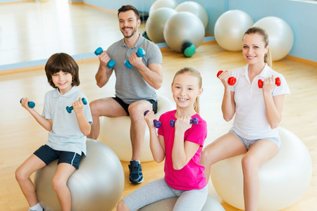 family health: Enjoying time in sorts club. Top view of happy sporty family exercising with dumbbells in sports club while sitting on the fitness balls together