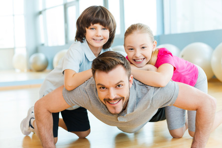Exercising with father. Happy little children bonding to their father doing push-ups in sports club photo