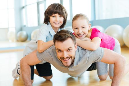 fathers: Hacer ejercicio con el padre. Peque�os ni�os felices uniendo a su padre haciendo flexiones en club deportivo