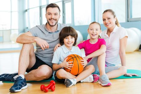 Feliz de ser una familia. Feliz unión de la familia deportiva entre sí mientras se está sentado en la estera de ejercicio juntos