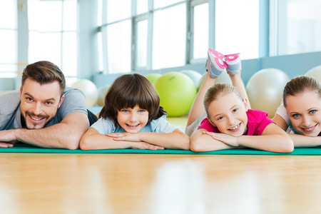 family exercise: Happy sporty family. Happy family bonding to each other while lying on exercise mat in sports club
