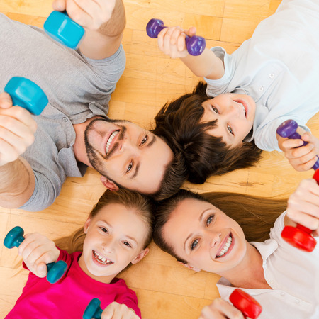 lifestyle caucasian: Living an active life. Top view of happy sporty family bonding to each other while lying on the floor and holding dumbbells