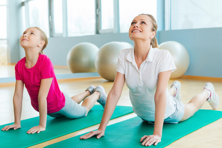 physical education: Warming up in sports club. Cheerful mother and daughter doing stretching exercises while lying on exercise mats in sports club Stock Photo