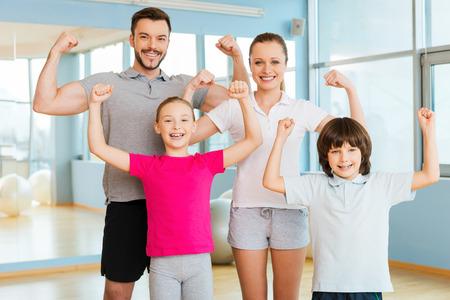 familias jovenes: Orgulloso de ser fuerte y saludable. Familia deportiva feliz que muestra sus b�ceps y sonriendo mientras est� de pie cerca uno del otro en el club deportivo