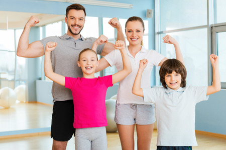 parent child: Proud to be strong and healthy. Happy sporty family showing their biceps and smiling while standing close to each other in sports club