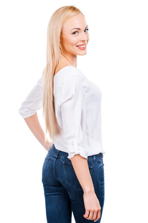 Confident in her perfection. Rear view of beautiful mature women looking over shoulder and smiling while standing against white background photo