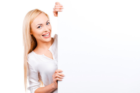 Your advertisement in her hands. Beautiful mature women holding hands on copy space and looking at camera while standing against white background Stock Photo