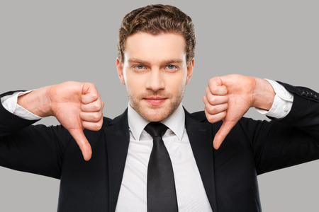 only adult: Bad news for you. Confident young man in formalwear showing his thumbs down and looking at camera while standing against grey background Stock Photo