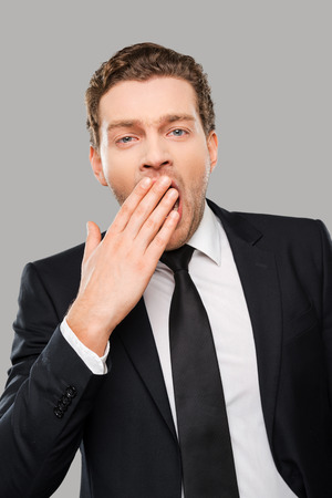 yawing: Feeling bored. Bored young man in formalwear covering his mouth by his hand and yawning while standing against grey background