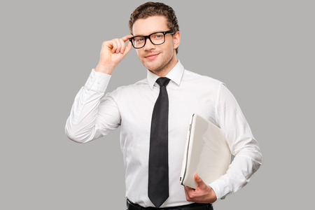 Businessman with laptop. Handsome young man in shirt and tie adjusting his eyewear and holding laptop while standing against grey background