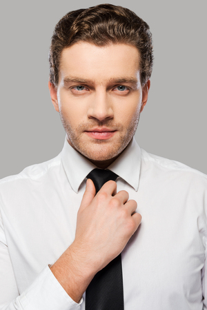 Making business look good. Confident young man in shirt and tie adjusting his necktie and looking at camera while standing against grey background photo