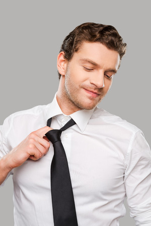tired businessman: Too much pressure. Frustrated young man in shirt and tie touching untying his necktie while standing against grey background Stock Photo
