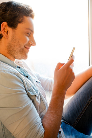 good news: Good news from friend. Side view of handsome young man sitting at the window sill and holding mobile phone
