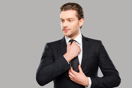 adjusting: Making business look good. Confident young man in formalwear adjusting his necktie and looking away while standing against grey background