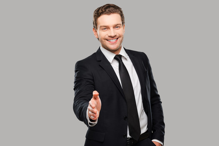 shaking out: Congratulations! Portrait of cheerful young man in formalwear stretching out hand for shaking while standing against grey background Stock Photo