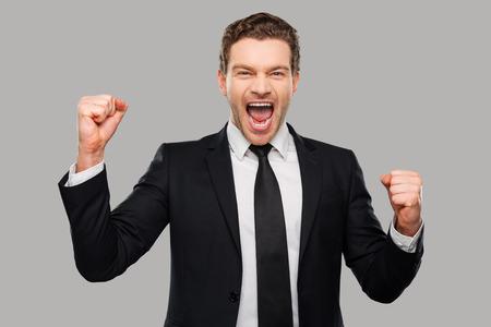 나는 승리를 사랑 해요! 회색 배경에 서있는 동안 몸짓 정장에 행복 한 젊은 남자 스톡 콘텐츠 - 38135629