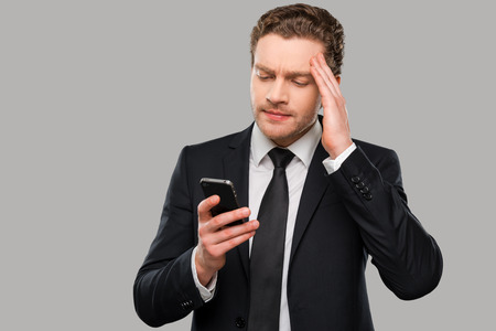 bad news: Bad news. Frustrated young man in formalwear holding mobile phone and touching head with hand while standing against grey background