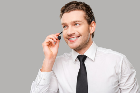 customer service representative: Confident customer service representative. Handsome young man in formalwear and headset looking away and smiling while standing against grey background