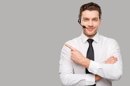 Exploitant wijzend kopie ruimte. Knappe jonge man in formalwear en headset kijken naar de camera en de weg te wijzen tijdens zich tegen grijze achtergrond