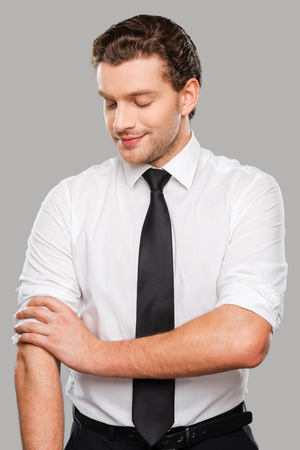 his shirt sleeves: Ready to work. Confident young man in shirt and tie adjusting his sleeves while standing against grey background