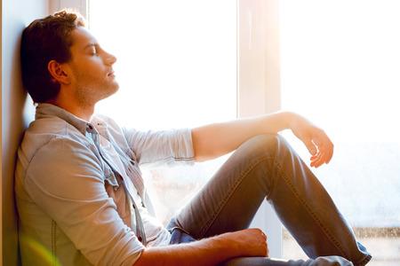 personas pensando: Relajaci�n total. Vista lateral del hombre joven y guapo sentado en el alf�izar de la ventana y manteniendo los ojos cerrados