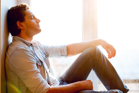 men shirt: Total relaxation. Side view of handsome young man sitting at the window sill and keeping eyes closed
