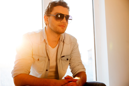 window sill: Taking time to relax. Handsome young man in sunglasses sitting at the window sill looking away