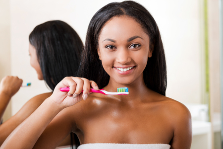 Teeth care. Beautiful young African woman brushing her teeth and smiling while standing against a mirror in bathroom photo