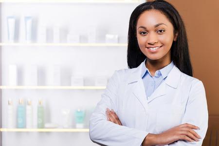farmacia: Confiado farmac�utico. Mujer africana joven hermosa en bata de laboratorio manteniendo los brazos cruzados y sonriendo mientras est� de pie en la farmacia Foto de archivo