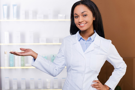 female hand: Make your choice. Beautiful young African woman in lab coat keeping arms crossed and smiling while standing in drugstore