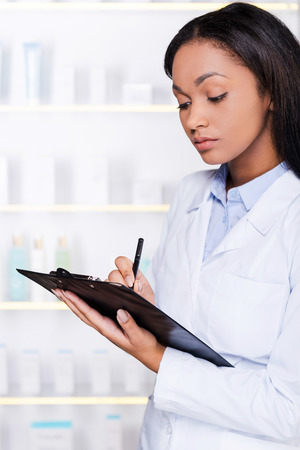 Pharmacist in drugstore. Confident young African woman in lab coat making notes in clipboard while standing in drugstore photo