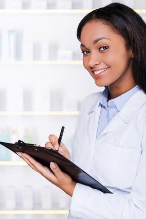bata de laboratorio: C�mo puedo ayudarte? Mujer africana joven confidente en bata de laboratorio haciendo notas en el portapapeles y sonriendo a usted mientras est� de pie en la farmacia