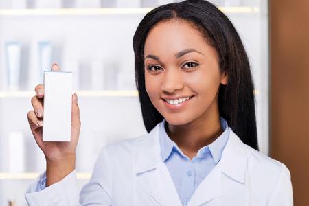 bata de laboratorio: Asesoramiento profesional. Mujer africana joven hermosa en bata de laboratorio sosteniendo recipiente con un poco de medicina y sonriendo mientras está de pie en la farmacia Foto de archivo