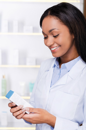 new medicine: Examining new medicine. Beautiful young African woman in lab coat holding container with some medicine and looking at it with smile while standing in drugstore Stock Photo
