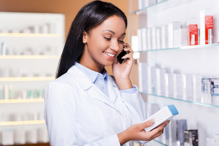Advising a proper medicine. Beautiful young African woman in lab coat holding container with some medicine and talking on the mobile phone while standing in drugstore