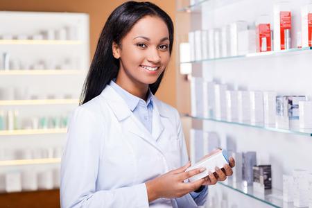 bata de laboratorio: Elecci�n profesional. Mujer africana joven hermosa en bata de laboratorio sosteniendo recipiente con un poco de medicina y mirando a c�mara con una sonrisa mientras est� de pie en la farmacia Foto de archivo