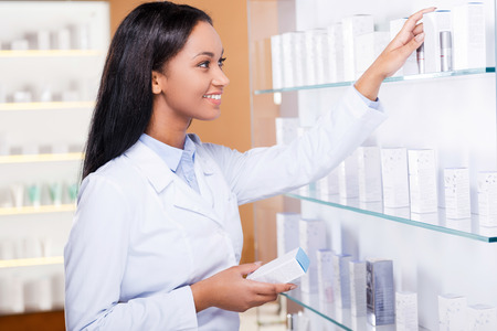health care decisions: Choosing the right medicine for you. Beautiful young African woman in lab coat choosing medicine while standing near the self in drugstore