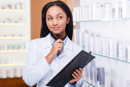 Thinking about a proper medicine for you. Thoughtful young African woman in lab coat holding clipboard and looking away with smile while standing near the shelf in drugstore