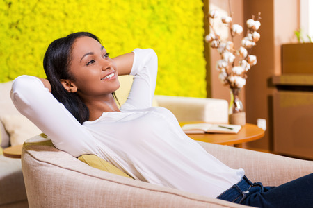 relaxing: Total relaxation. Attractive young African woman holding hands behind head and smiling while sitting at the chair at home