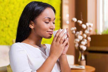 nariz: Disfrutar caf� fresco. Vista lateral de la joven y bella mujer africana que sostiene la taza de caf� cerca de la nariz y sonriendo mientras mantiene los ojos cerrados y se sienta en la silla en su casa