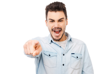 beautiful angry: You are wrong! Frustrated young man pointing you and shouting while standing against white background