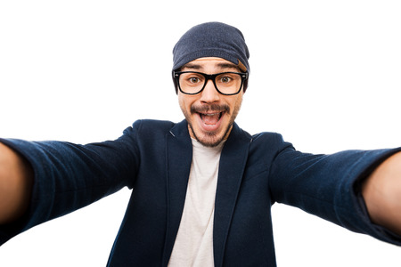 Just me! Cheerful young man in eyewear and hat making selfie while standing against white background