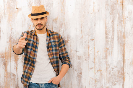 fedora hat: He chooses you. Portrait of handsome young man looking and pointing at camera while standing against the wooden wall