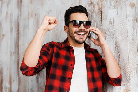 good news: He likes good news. Portrait of cheerful young man talking on the mobile phone and smiling while standing against the wooden wall Stock Photo