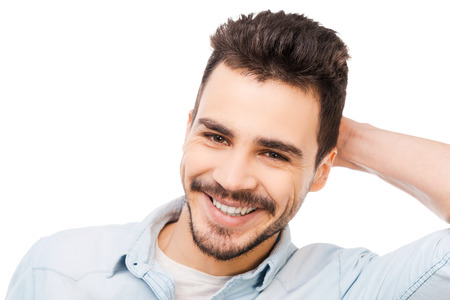 Candid smile. Handsome young man touching his head and smiling while standing against white background