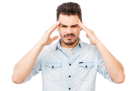 Too much stress. Frustrated young man touching head with fingers and looking at camera while standing against white background photo