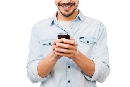 Communicative person. Cropped picture of handsome young man holding mobile phone and smiling while standing against white background