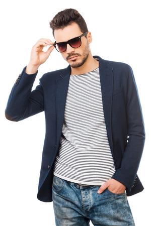 modelos hombres: Confiados en su estilo. Apuesto joven ajustando sus gafas de sol de pie contra el fondo blanco