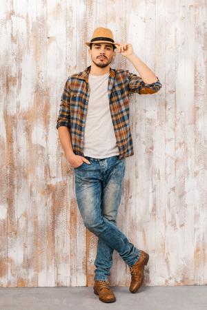 hombre con sombrero: Serio y confiado. Longitud total de hombre joven y guapo que ajusta su sombrero y mirando a la c�mara mientras est� de pie contra la pared de madera