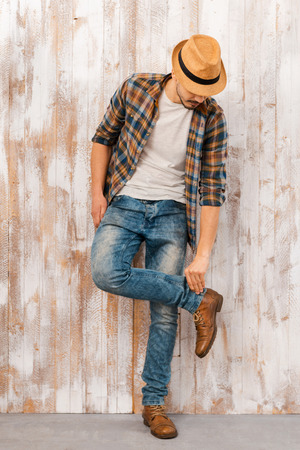Everything should be perfect. Full length of handsome young man adjusting his jeans while standing against the wooden wall